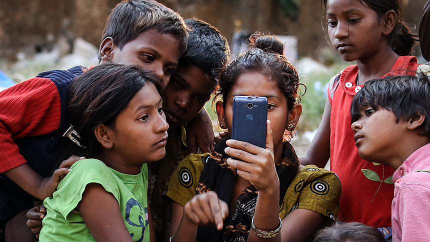 "Indian children watch a movie on a cellphone on the roadside in Mumbai Jan. 20, 2016. While digital communications and social media can be used as a tool of evangelization and a place of dialogue with others, they also can be lonely environments where young people fall prey to humanity's worst vices, Pope Francis wrote in his new apostolic exhortation to young people, ""Christus Vivit"" (""Christ Lives""). (CNS photo/Divyakant Solanki, EPA)"
