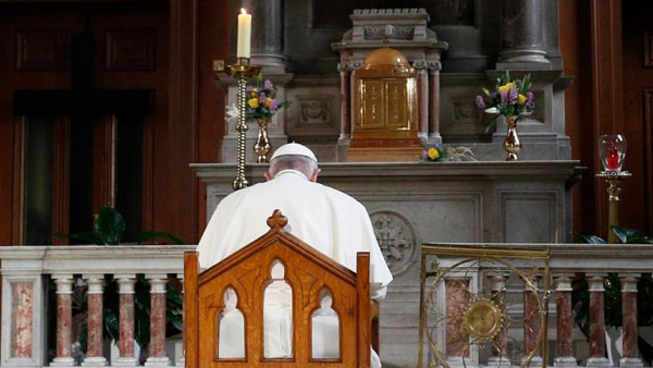 Pope Francis prays in front of a candle in memory of victims of sexual abuse as he visits St. Mary's Pro-Cathedral in Dublin Aug. 25, 2018.