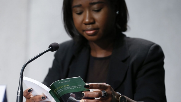 "Laphidil Oppong Twumasi, a youth leader from Ghana, reads Pope Francis' apostolic exhortation, ""Christus Vivit"" (Christ Lives), during a news conference for its presentation at the Vatican April 2, 2019. The document contains the pope's reflections on the 2018 Synod of Bishops on young people, the faith and vocational discernment. (CNS photo/CNS photo/Paul Haring)"