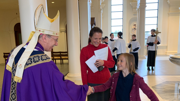 Bishop Zarama greets student at Homeschool Mass