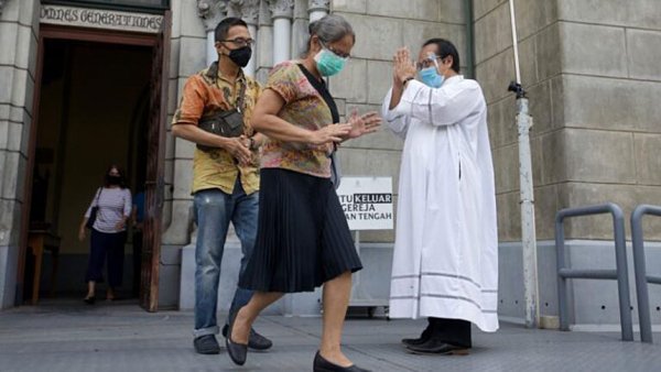 CNS: Priest wearing a protective face mask greets parishioners